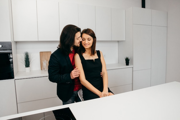 Couple in love tenderly hugs in a cozy home environment in the kitchen