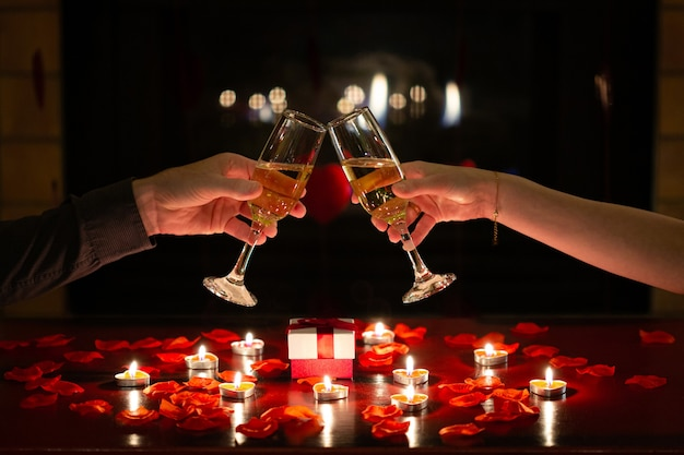 Couple in love toasting together with glasses of champagne to celebrate valentines day during romantic dinner red roses gifts and flowers
