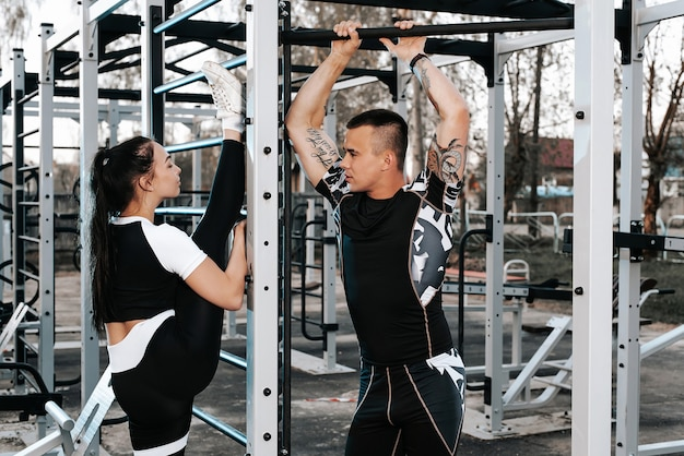 Couple in love train together on the horizontal bars and play sports on the sports field