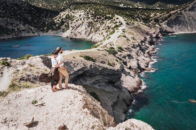 A couple in love travels. man and woman at the sea. travelers. man and woman have a rest abroad. the relationship between a man and a woman. woman hugging man. business abroad. honeymoon trip. in love