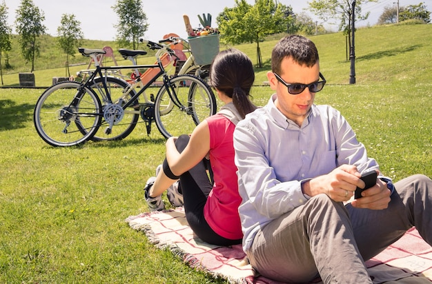 Couple in love using a smartphones on the park