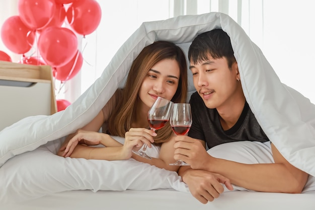 Couple, love and valentine's day concept. portrait of a couple on bed in white blanket and holding glass of red wine in bedroom with red balloon.