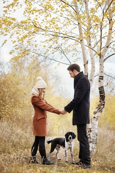 Couple in love on valentine's day walking in the park with the dog