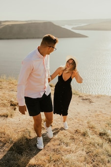 Couple in love walk on a mountain above a large lake by the sea at sunset.