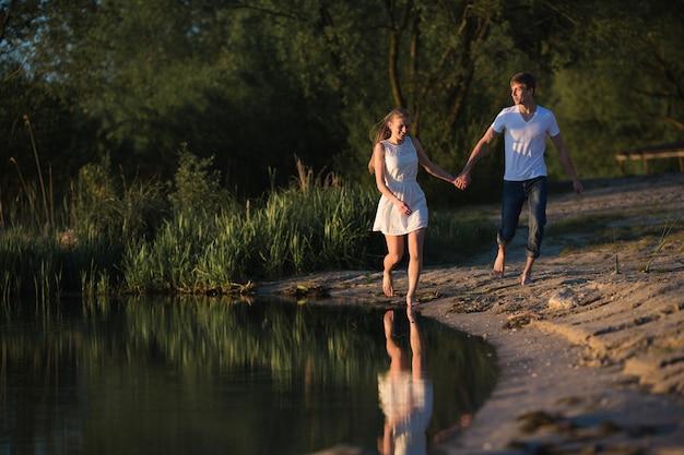 Coppia in amore camminando lungo la riva