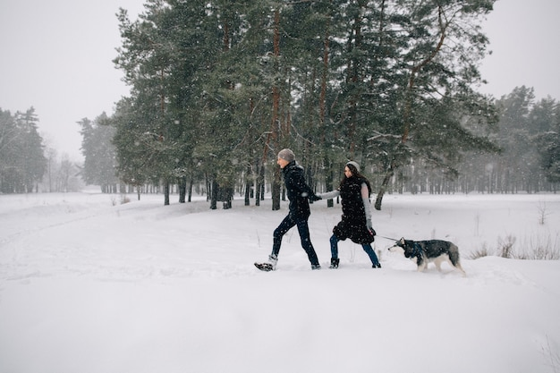 Couple in love walking with their husky dog in snowy winter weather
