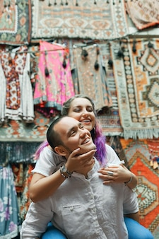 Couple in love walks and hugs at the eastern carpet market. a man and a woman choose a turkish carpet