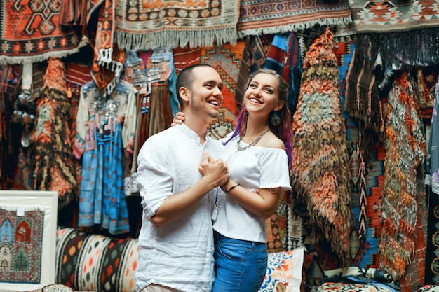 Couple in love walks and hugs at the eastern carpet market.