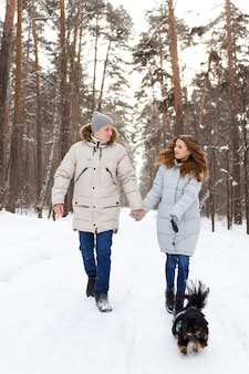 A couple in love walks their dog in the winter forest