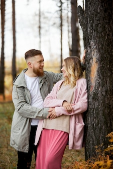 Couple in love walks through autumn forest. hugs and kisses of men and women, relationships and love. young couple stands in yellow red grass, a bouquet of flowers in girl hand