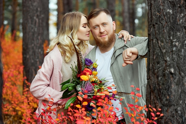 Couple in love walks through autumn forest. hugs and kisses of men and women, relationships and love. young couple stands in yellow red grass, a bouquet of flowers in woman hand