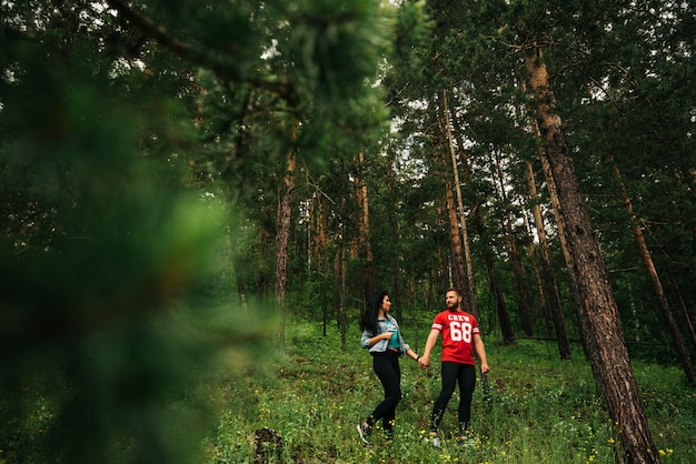 A couple in love walks through the coniferous forest. guy and girl walking in the woods. man and woman holding hands. couple in green forest. the couple in love hold hands in the forest. follow me