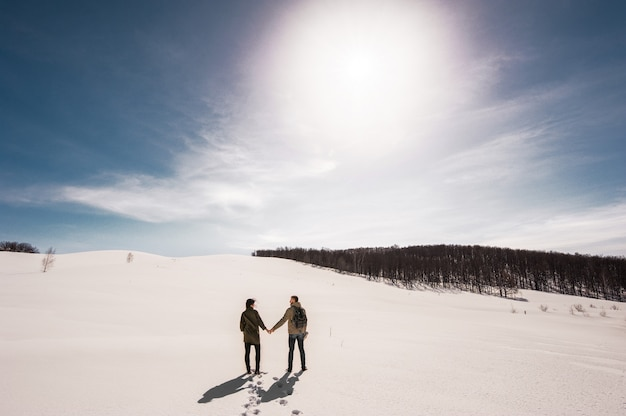 Couple in love walks in winter in the snow. man and woman traveling. couple in love in the mountains. travelers in the mountains. winter walk. winter adventures. winter walk. loving couple