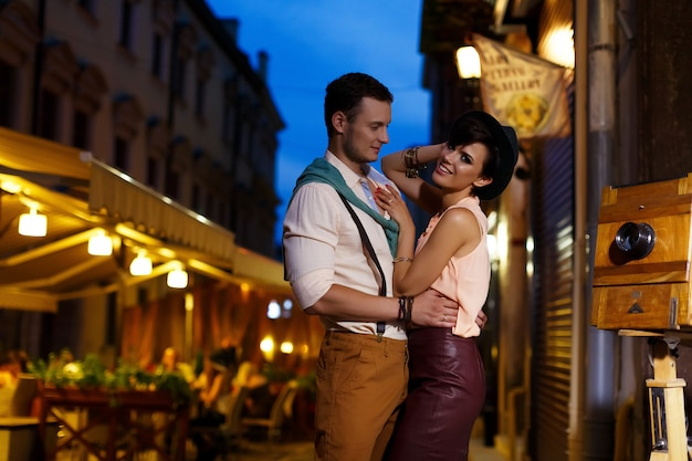 Couple in love while walking in the night city cuddling on the street