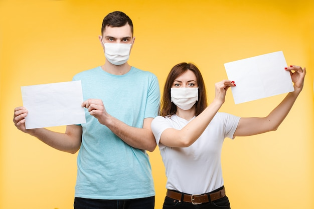 Couple in love in white medical masks are scared by coronavirus and shows posters