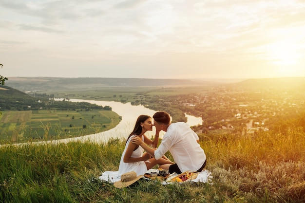 Couple in love on a white plaid on the mountain at a picnic