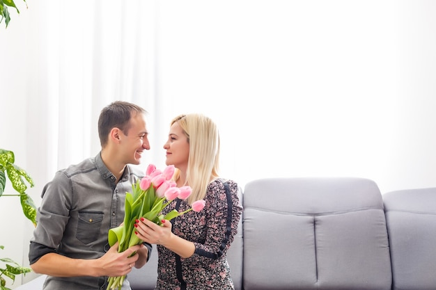 Couple in love with a bouquet of tulips are close to each other