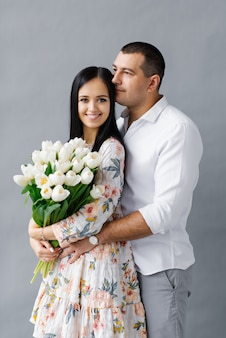 A couple in love with a bouquet of tulips in the studio on a gray background, the concept of valentine's day