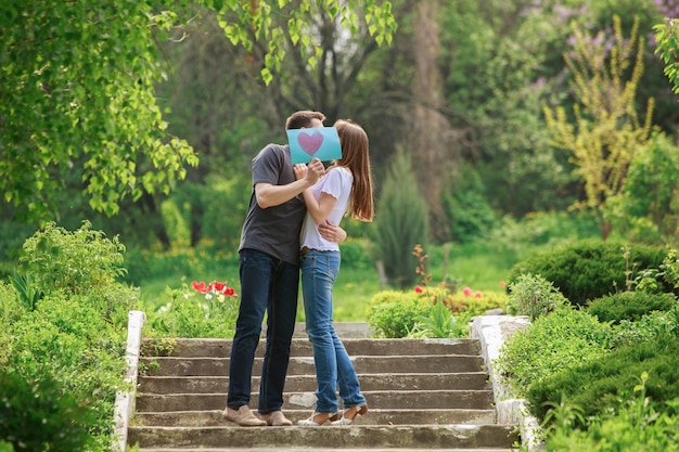 Couple in love with greeting card with heart outdoor. love story concept. romantic date in nature