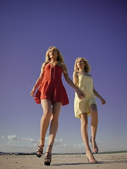 Couple in love. women with blonde hair outdoor. girls with sexy legs, family and sisters. freedom and family values. beauty and fashion, look. twins in summer walk on blue sky background.