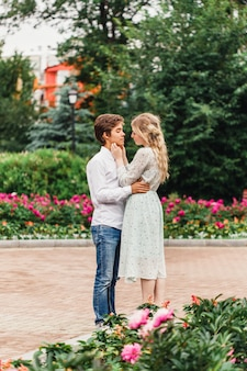 A couple in love, a young girl and a man, standing in the park, hugs, meeting, kissing, bouquet