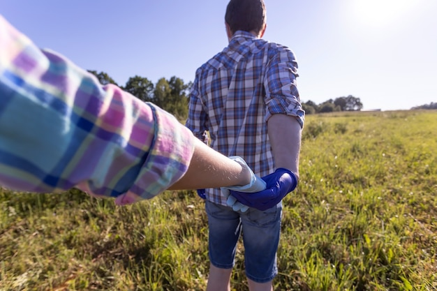 A couple in lovea man and a woman hold hands in nature during a walk in a new reality