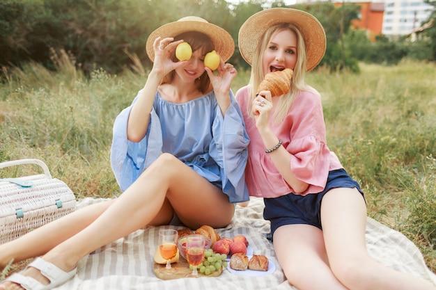 Coppia di belle donne graziose in posa sul prato nel parco estivo, gustando cibo gustoso, croissant e vino. amici che godono del picnic.