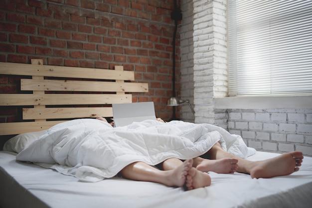 カップルの恋人はベッドで寝ています。タブレットでオンラインで映画を見る