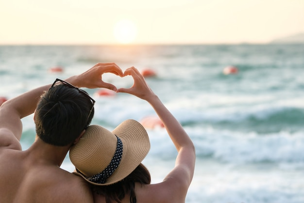 Couple lover make hand lover on the sunset beach