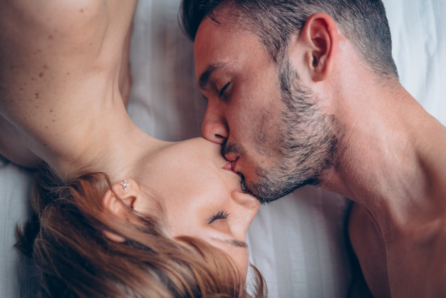 Couple of lovers having sexy and romantic kiss at home on the bed at morning.