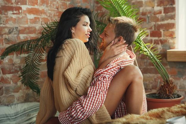 Coppia di innamorati a casa che si rilassano insieme. l'uomo e la donna caucasici che hanno fine settimana, sembrano teneri e felici. concetto di relazioni, famiglia, comfort autunnale e invernale. romantico domestico.