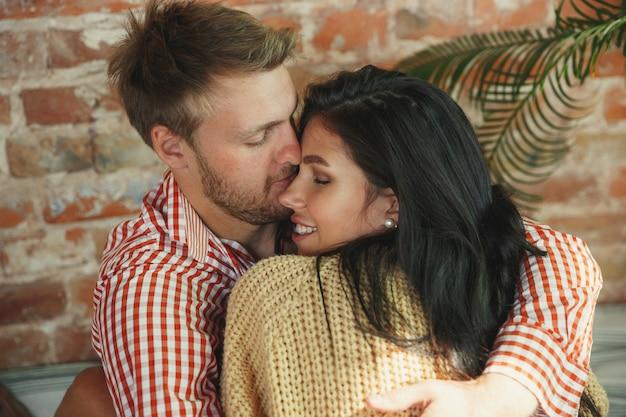 Coppia di innamorati a casa che si rilassano insieme. l'uomo e la donna caucasici che hanno fine settimana, sembrano teneri e felici. concetto di relazioni, famiglia, comfort autunnale e invernale. abbracciare e baciare, da vicino.
