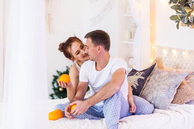 Couple of lovers in pajamas lying on the sofa. christmas time. holiday at home