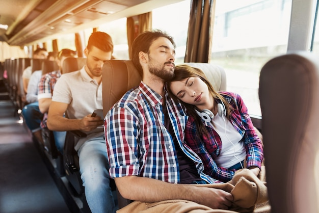 Couple of lovers sleeps in modern travel bus.