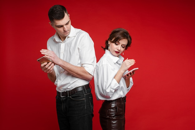 Couple of lovers surfing internet and closes phone screens from each other