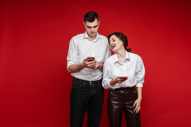 Couple of lovers surfing internet and smiles, picture isolated on red wall