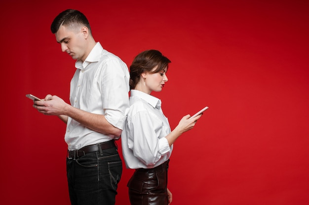Couple of lovers surfing internet and stands back to each other, picture isolated on red wall