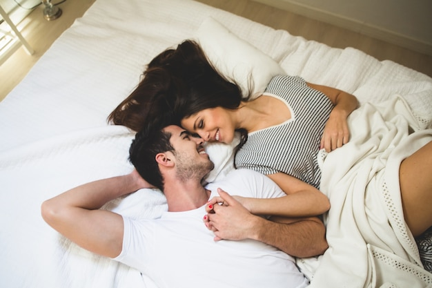 Couple lying on the bed holding hands and looking into each other's eyes