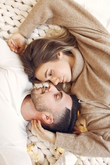 Couple lying on a bed in a room