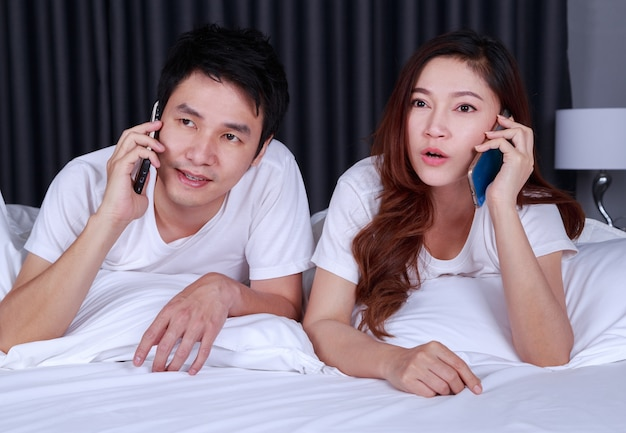 Couple lying in bed and talking on mobile phone