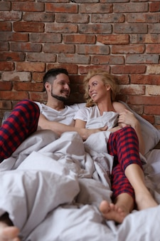 Couple lying on the bed in twin pijamas and laughing