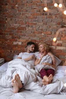 Coppia sdraiata sul letto in pigiama gemello e parlando
