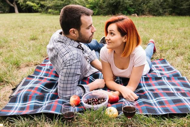 Couple lying on blanket over green grass enjoying fruits
