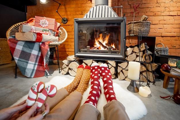 Пара, лежа у горящего камина, украшенного для новогодних праздников в уютном домашнем интерьере