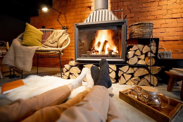 Пара, лежа у горящего камина в уютном доме в стиле лофт
