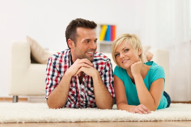 Couple lying down on carpet at home