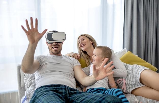 Пара лежит со своим ребенком и смотрит что-то в гарнитуре виртуальной реальности