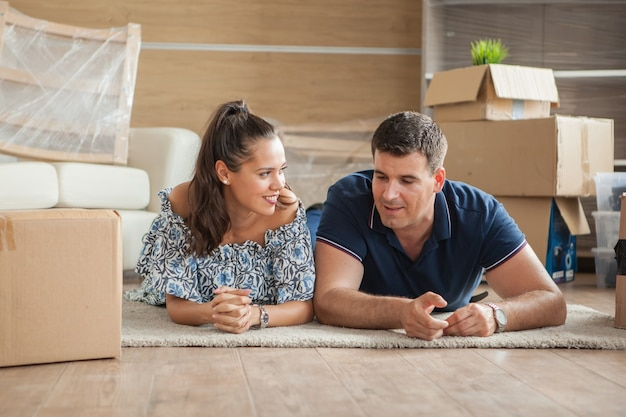 彼らの新しい家の床に幸せに横たわっているカップル。住宅ローンと家族
