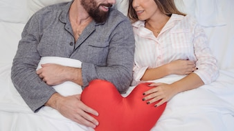 Couple lying in bed with toy heart