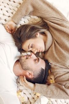 部屋のベッドに横たわっているカップル